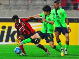 Chang-Soo (centre) tackles Adriano (left) during their AFC Champions League semi-final. AFP