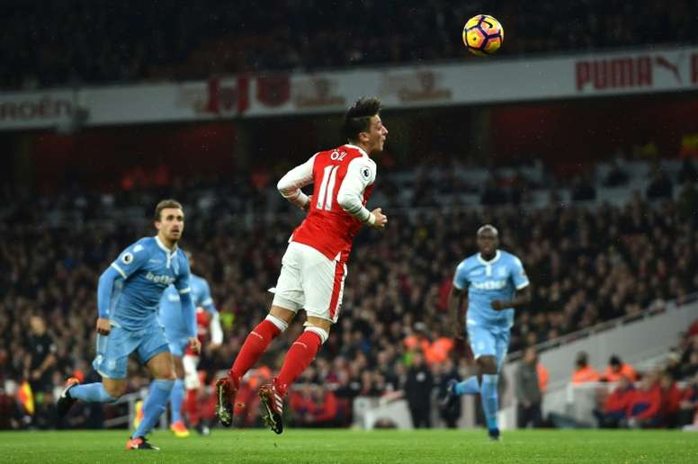 Arsenals Mesut Ozil (C) heads the ball to score a goal during their English Premier League match against Stoke City, at the Emirates Stadium in London, on December 10, 2016