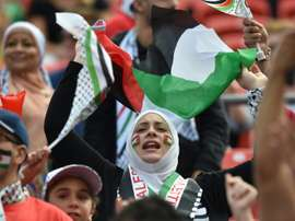 Palestinian fans cheer before a match on January 12, 2015