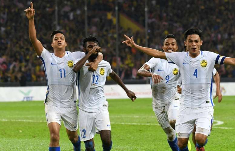 Malaysian players celebrate their goal against Indonesia. AFP