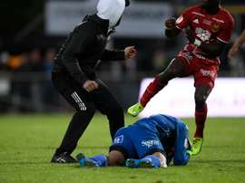 Ostersund's Aly Keita lies on the ground after a masked spectator attacked him during a match. AFP