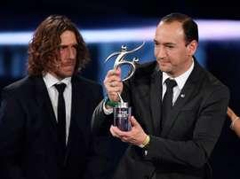 Colombian executive and chairman of Atletico Nacional Juan Carlos de la Cuesta (R) holds The 2016 FIFA Fair Play Award next to former Spanish football player Carles Puyol during The Best FIFA Football Awards ceremony, on January 9, 2017 in Zurich