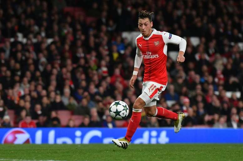 Arsenal midfielder Mesut Ozil shoots to score his hat trick and his teams sixth goal. AFP