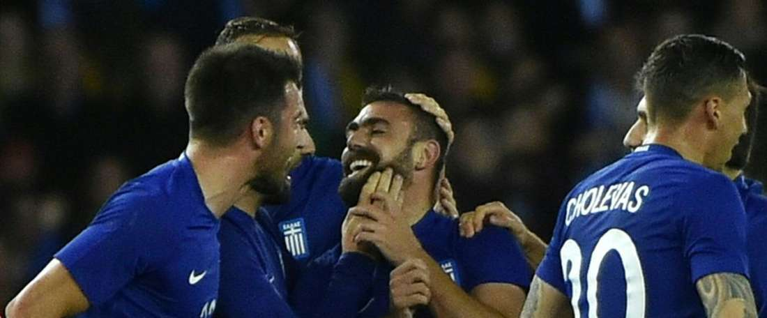Greek midfielder Ioannis Maniatis (centre) is mobbed by his team-mates after scoring. BeSoccer