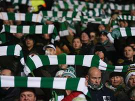 Celtic fans hold up team scarves in Glasgow. AFP