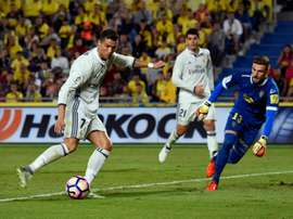 Real Madrids forward Cristiano Ronaldo (L) vies with Las Palmas goalkeeper Raul Lizoain Cruz at the Gran Canaria stadium in Las Palmas de Gran Canaria on September 24, 2016.