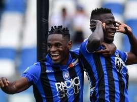 Duvan Zapata celebrates a goal with Musa Barrow. AFP