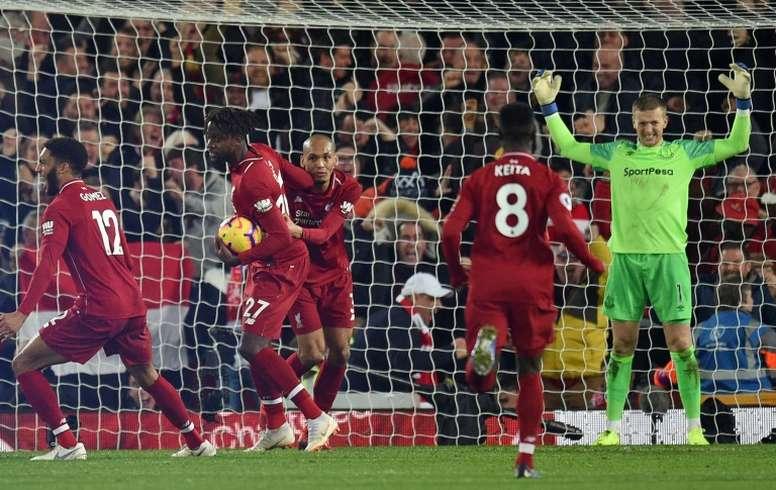 Liverpool players celebrate Divock Origi's late winning goal against Everton. AFP