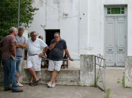 Friends console Emiliano Sala's father Horatio (second from right) outside his house. AFP