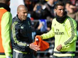 Real Madrid forward Cristiano Ronaldo (R) gives a bib to new French coach Zinedine Zidane during his first training session as coach at the Alfredo di Stefano stadium in Valdebebas, on the outskirts of Madrid, on January 5, 2016