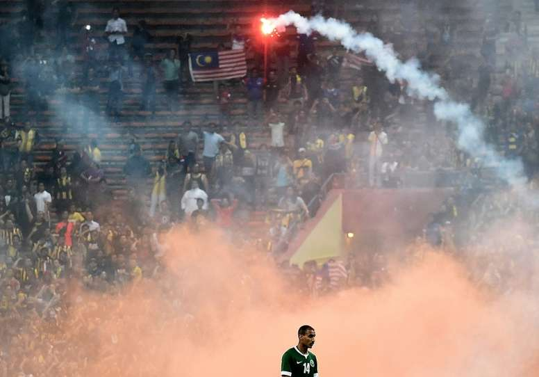 Yasyn Alnakhli of Saudi Arabia walks off the pitch after flares were thrown by football fans during the 2018 World Cup qualifying match between Malaysia and Saudi Arabia in Shah Alam on September 8, 2015