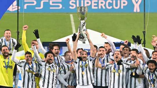 Giorgio Chiellini (C) lifts the trophy after Juventus beat Napoli to win the Italian Super Cup. AFP