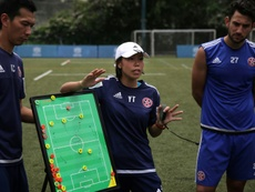 Head coach of Eastern FC, Chan Yuen-ting, talks to her players during a training session. AFP