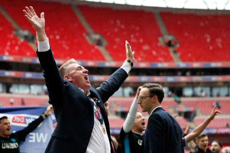 Dean Smith celebró con rabia y alegría el ascenso de los 'villanos'. AFP