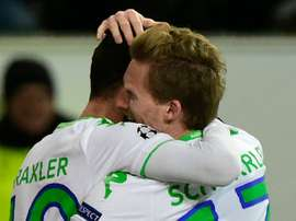 Wolfsburgs striker Andre Schuerrle (R) and Julian Draxler react after scoring during a UEFA Champions League match against Gent at the Volkswagen arena in Wolfsburg on March 8, 2016