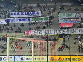 Football fans display banners protesting against Jeonbuk Hyundai Motors bribing of referees. AFP