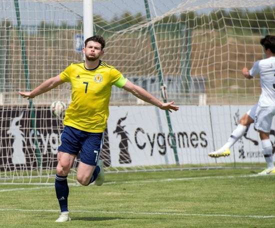 Oliver Burke tapped in to seal a victory that sees Scotland move up to third. AFP