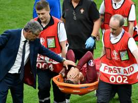 Portugals forward Cristiano Ronaldo is comforted by Portugals coach Fernando Santos as he is carried on a stretcher off the pitch by team medics after an injury following a clash with Frances forward Dimitri Payet during the Euro 2016 final