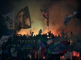 Inter Milan supporters light fireworks during the Italian Serie A football match Inter Milan vs AC Milan at the San Siro Stadium in Milan on April 19, 2015