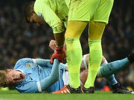 Manchester Citys midfielder Kevin De Bruyne (L) reacts as he talks with Evertons goalkeeper Joel Robles before being stretchered off during an English League Cup semi-final match at the Etihad Stadium in Manchester on January 27, 2016