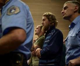 Leutrim Musliu et Besart Peci (au centre) sont encadrés par les forces de sécurité. AFP