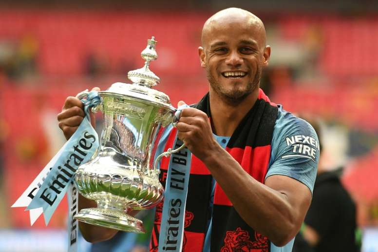 Vincent Kompany with the third of his 3 trophies this season. AFP