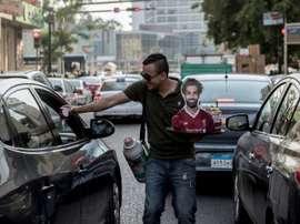 Un vendeur ambulant,portrait de M. Salah à la main, le 17/06/19. AFP