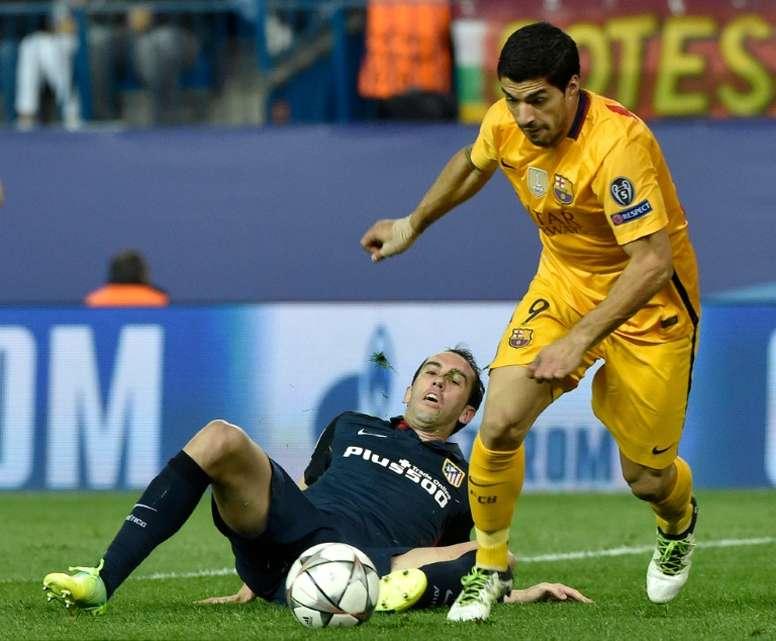 Godín y Suárez, pese a su amistad, van a por todas en el césped. AFP