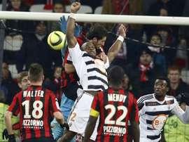 Le défenseur de Lorient Lamine Koné (c) à la lutte avec le défenseur de Nice Paul Baysse à lAllianz Riviera, le 23 janvier 2016
