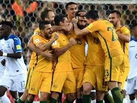 Os jogadores da Austrália rodeiam o seu capitão em acesa celebração. AFP