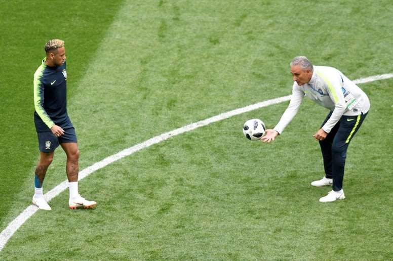 Neymar, arropado por Tite. AFP/Archivo