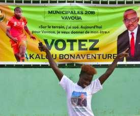 Une Ivoirienne danse devant l'affiche électorale de Bonaventure Kalou. AFP