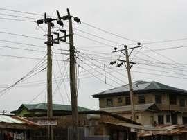Poteaux électriques, transformateurs et panneaux solaires surplombent des immeubles de Lagos. AFP
