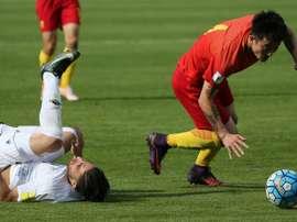 Le Chinois  Zhipeng trébuche sur l'Iranien Jahanbakhsh au cours du match de qualification. AFP