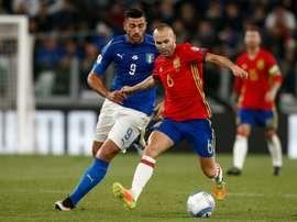 Graziano Pellè à la lutte avec le milieu espagnol Andres Iniesta lors des qualifs. AFP