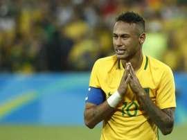 Neymar la toma con un aficionado en la celebración del oro. AFP