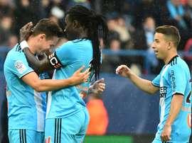 Florian Thauvin félicité par son capitaine Bafé Gomis après un de ses trois buts à Caen. AFP