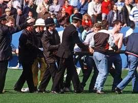 Des policiers transportent un supporter blessé dans le stade de Hillsborough. AFP