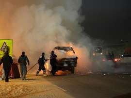 Des pompiers saffairent autour dun véhicule en feu après des incidents près dun stade au Caire. AFP