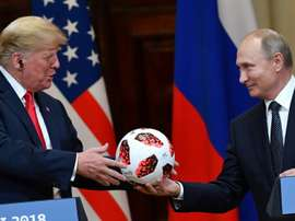 Le président russe Vladimir Poutine offre un ballon au président américain Donald Trump. AFP