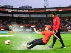 Un jeune volontaire de l'Euro glisse dans une flaque d'eau. AFP