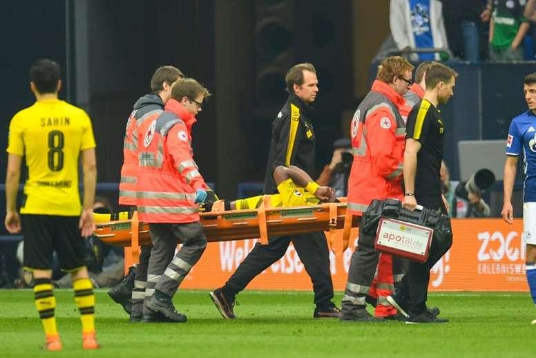 Batshuayi, retirado en camilla ante el Schalke 04. AFP