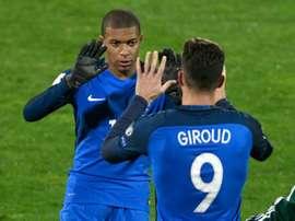 Olivier Giroud croise Kylian Mbappé lors de son remplacement. AFP