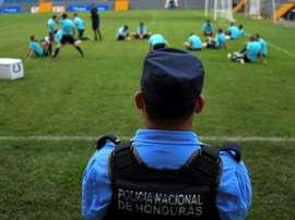 Un membre de la police hondurienne surveille l'entraînement de l'équipe d'Australie. AFP