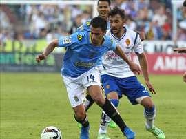 El centrocampista del UD Las Palmas Hernán Santana (i) y el defensa del Real Zaragoza Mario Abrante, durante el partido de ida de la final para el ascenso a Primera División, que disputaron en el estadio de la Romareda. EFE