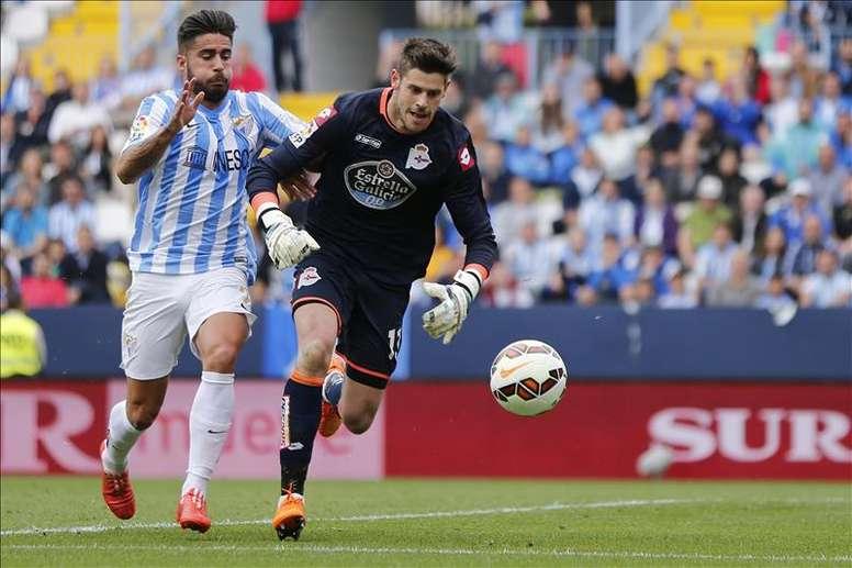 El portero del Deportivo Fabricio Agosto corre hacia el balón en presencia del delantero del Málaga Samuel García Sánchez. EFE/Archivo