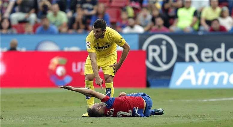 El defensa esloveno del Villarreal Bojan Jokic (arriba) hace un gesto hacia al defensa del Levante Iván López, tras una entrada que le costó la tarjeta roja, durante el partido de la séptima jornada de Liga jugado en el estadio Ciutat de Valencia. EFE