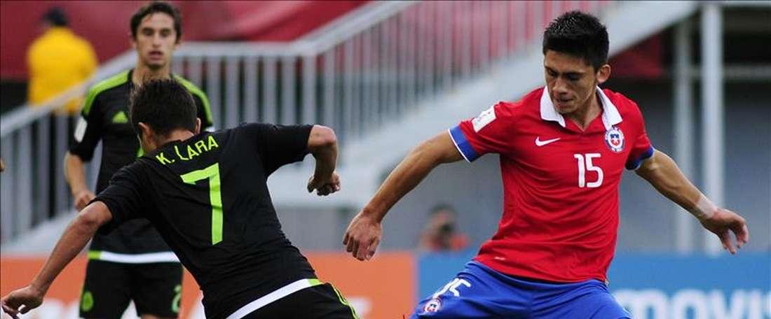 El jugador chileno Rene Meléndez (d) disputa el balón con el mexicano Kevin Lara (i) este 28 de octubre de 2015, en el partido de octavos de final entre Chile y México por el torneo mundial de fútbol sub17, en el estadio Nelsón Oyarzún, en Chillán (Chile). EFE