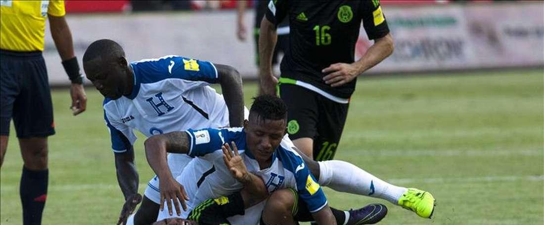En la imagen, el jugador mexicano Javier Aquino (abajo) disputa el balón con los hondureños Wilmer Crisantos (i) y Luis Garrido (c) durante un partido por las eliminatorias de la Copa Mundial de la FIFA Rusia 2018, en el estadio Olímpico de San Pedro Sula (Honduras). EFE/Archivo