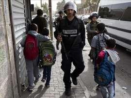 Varios niños caminan junto a agentes de la policía israelí de fronteras en la zona del Monte de los Olivos en Jerusalén. EFE/Archivo